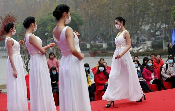 Models wearing masks present jewellery on a runway at a jewellery fair on a hazy day in Nanjing, Jiangsu province, Dec. 6, 2013. REUTERS/Stringer