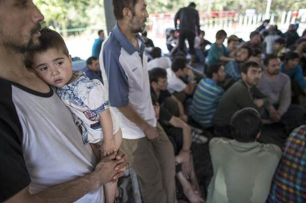 A suspected Uighur from China's troubled far-western region of Xinjiang, holds his son at a temporally shelter after they were detained at the immigration regional headquarters near the Thailand-Malaysia border in Hat Yai, Songkla March 14, 2014 REUTERS/Athit Perawongmetha