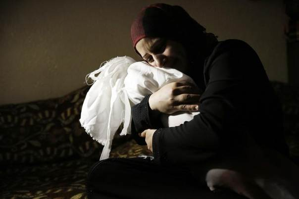 Netream Netzleam holds the body of her daughter Razel, 1, who medics said died from injuries sustained in an Israeli air strike, at her funeral in Rafah in the southern Gaza Strip, July 18, 2014. REUTERS/Finbarr O'Reilly