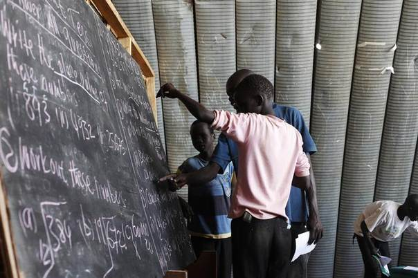 A teacher explains the lesson to students in a classroom inside the UN House IDP camp in Juba, July 8, 2014. REUTERS/Andreea Campeanu