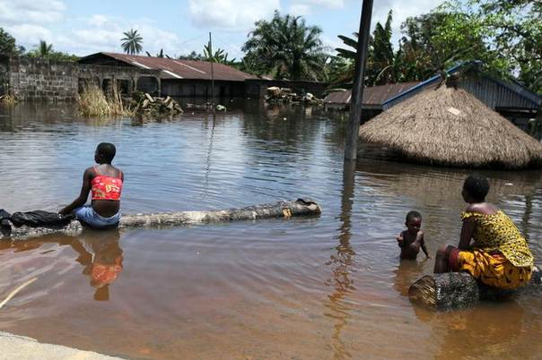 People sit in front of a submerged building in the Patani community in Nigeria's Delta state October 15, 2012. REUTERS/Afolabi Sotunde