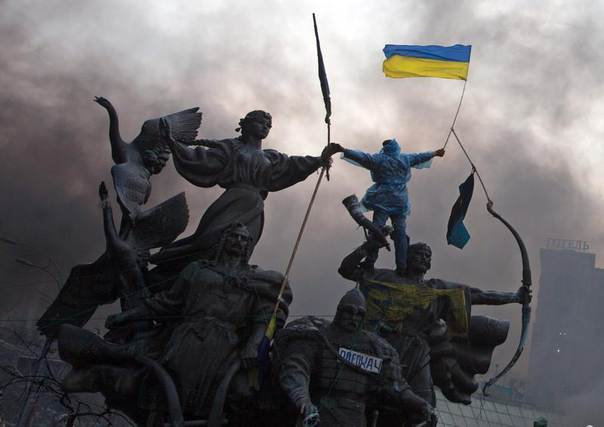 An anti-government protester waves the national flag from the top of a statue during clashes with riot police in the Independence Square in Kiev, Ukraine, February 20, 2014. REUTERS/Stringer