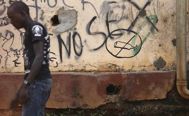 A man walks past graffiti about sex in downtown Kampala March 7, 2014 REUTERS/Edward Echwalu