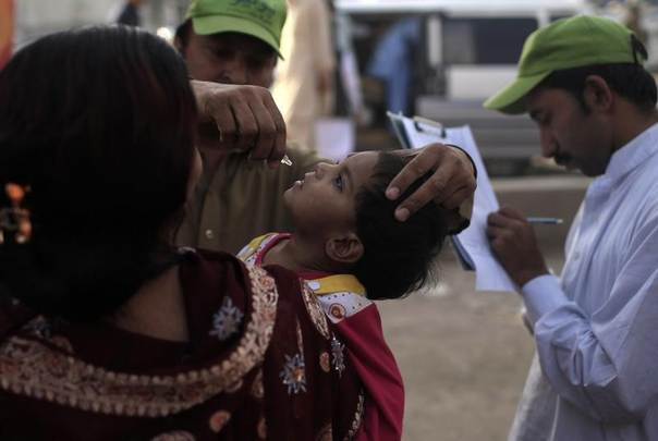 A polio worker administers polio vaccine to a child in Rawalpindi, Pakistan May 13, 2014. REUTERS/Sara Farid