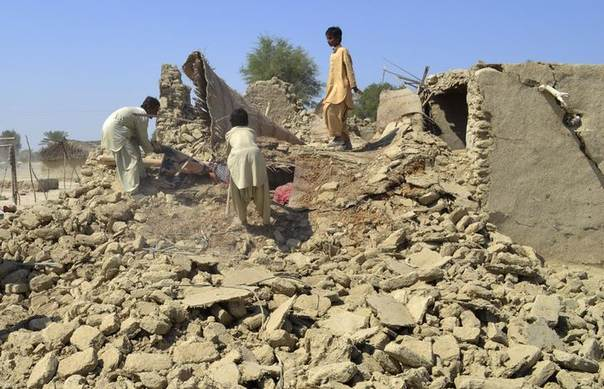 Survivors collect their belongings from the rubble of a mud house after it collapsed following an earthquake in the town of Awaran, southwestern Pakistani province of Baluchistan, September 25, 2013 REUTERS/Naseer Ahmed