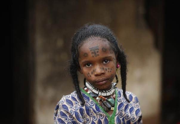 A Muslim girl, who is protected by local Christians, stands outside a house in town of Yaloke, northwest of Bangui, April 5, 2014. REUTERS/Goran Tomasevic