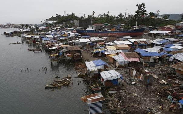 A view of temporary shelters for typhoon survivors constructed next to a ship that ran aground, nearly 100 days after super Typhoon Haiyan devastated Tacloban city in the central Philippines Feb. 14, 2014. REUTERS/Erik De Castro