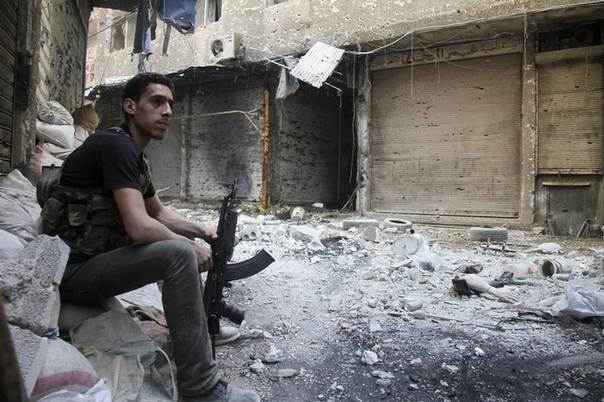 A Free Syrian Army fighter sits on sandbags in the refugee camp of Yarmouk, near Damascus, May 5, 2013. REUTERS/Ward Al-Keswani