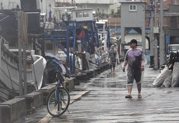 Fishermen in raincoats walk past fishing boats as Typhoon Matmo approaches the northeastern coastal town of Nanfangao in Ilan county, northern Taiwan, July 22, 2014 REUTERS/Pichi Chuang