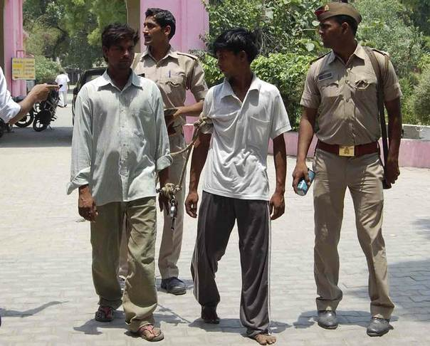 Indian policemen show two men (L and 2nd R), who are accused of gang raping and hanging two girls, to the media at Budaun district in the northern Indian state of Uttar Pradesh May 30, 2014. REUTERS/Stringer