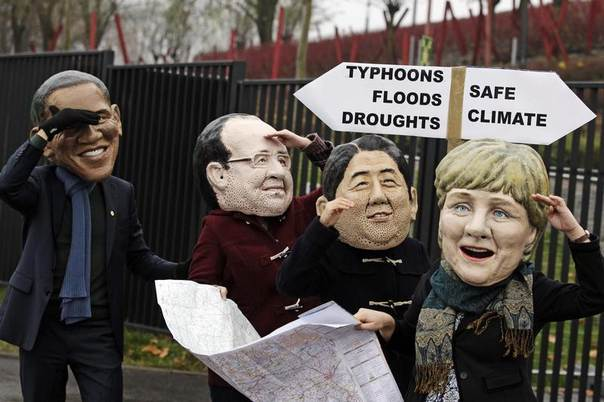 Protesters wearing masks of US President Barack Obama (L-R), France's President Francois Hollande, Japan's Prime Minister Shinzo Abe and German Chancellor Angela Merkel hold a map and a sign in front of the national stadium on the last day of U.N. climate talks in Warsaw, Nov. 22, 2013. REUTERS/Kacper Pempel