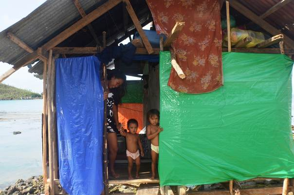 A family peeks out of a makeshift shelter on the Philippine coast in Marabut, Eastern Samar, after their dilapidated house was devastated by Typhoon Haiyan in November 2013. TRF/Imelda Albano