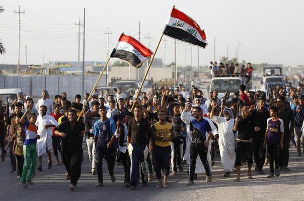Volunteers, who have joined the Iraqi Army to fight against predominantly Sunni militants from the radical Islamic State of Iraq and the Levant (ISIL), carry their weapons and wave the Iraqi flags during a parade in the streets in Al-Fdhiliya district, eastern Baghdad June 15, 2014 REUTERS/Thaier Al-Sudani