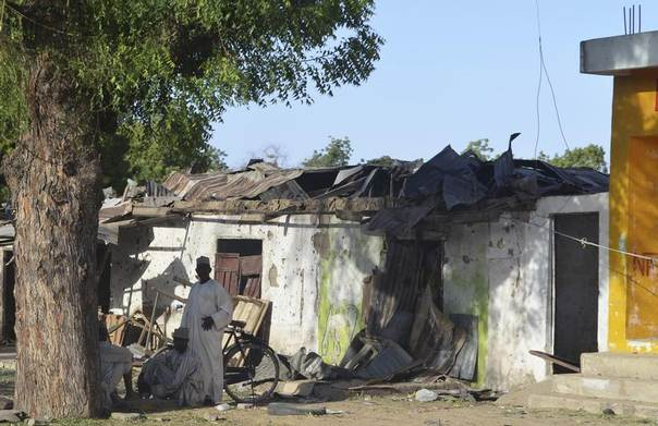 Men sit infront of a house that was damaged during an attack by Boko Haram militants in Bama, Borno State, Nigeria, February 20, 2014. REUTERS/Stringer