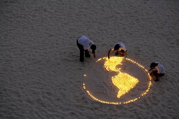 World Wildlife Fund (WWF) activists light candles representing the earth as they demonstrate on the sidelines of the UN Climate Change Conference in Cancun, Dec. 5, 2010. REUTERS/Gerardo Garcia