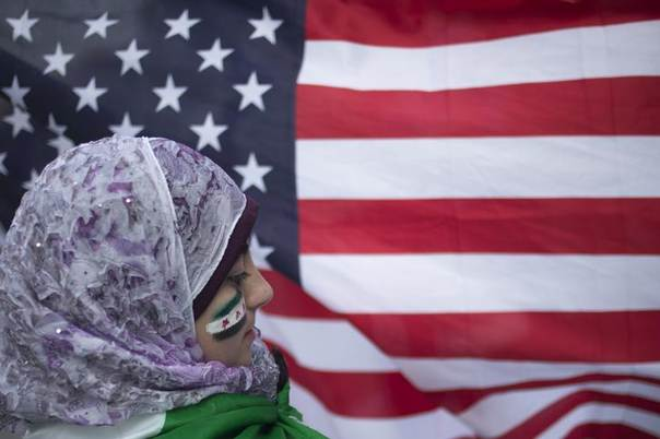 With cheeks painted in the colors of Syria's flag, 13-year-old displaced Syrian girl Malek Al Rifai stands in front of a U.S. flag while taking part in a protest in front of the United Nations building in New York August 21, 2013. REUTERS/Adrees Latif