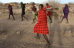 Turkana tribesmen walk with guns to protect their cattle from rivals in Kenya