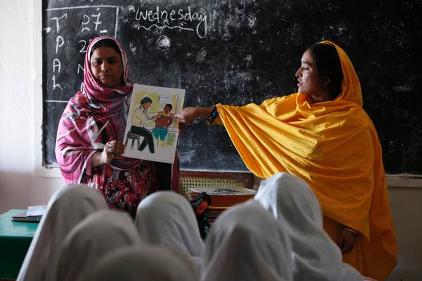 Pakistani teachers display a card depicting a girl undergoing a medical checkup during a class at Shadabad Girls Elementary School in rural Johi on February 12, 2014. REUTERS/Akhtar Soomro