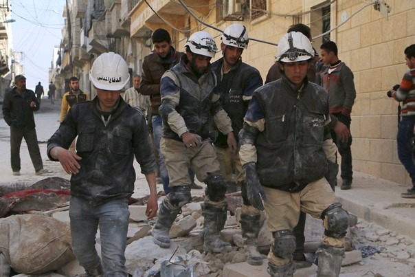 Rescuers walk on the rubble of collapsed buildings at a site hit by what activists said was an airstrike by forces loyal to Syrian President Bashar al-Assad in Masaken Hanano in Aleppo, Syria, February 14, 2014. REUTERS/Hosam Katan
