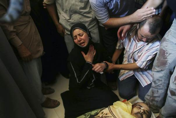Palestinian daughter of Tawfiq al-Aga, who medics said was killed in Israeli shelling, mourns next to her father body during his funeral in Khan Younis in the southern Gaza Strip July 23, 2014 REUTERS/Ibraheem Abu Mustafa