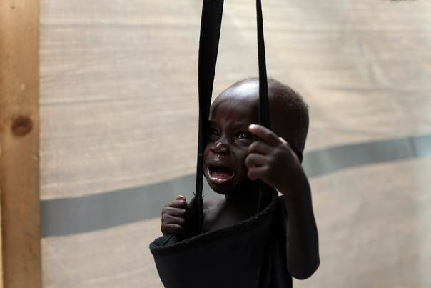 A South Sudanese child, suspected of malnutrition, cries while being weighed at a feeding center in Lul, Fashoda county in the Upper Nile State, on May 29, 2014. REUTERS/Andreea Campeanu