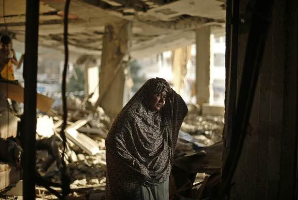 A Palestinian woman reacts next to debris in her house, which police said was targeted in an Israeli air strike, in Gaza City July 17, 2014. REUTERS/Mohammed Salem