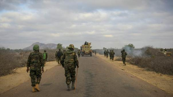 Ugandan soldiers serving with the African Union Mission in Somalia (AMISOM) walk along a road during an advance on the central Somali town of Buur Hakaba, in this handout photograph taken and provided by the African Union-United Nations Information Support Team (AU-UN IST) on February 27, 2013. REUTERS/Stuart Price/AU-UN IST PHOTO/Handout