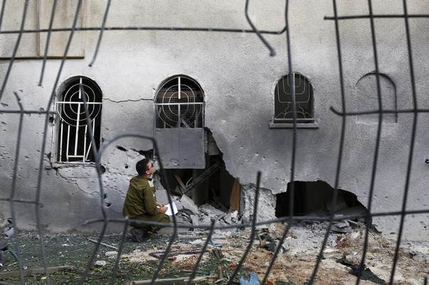 An Israeli soldier surveys the damages of a synagogue which was hit by a rocket in the southern city of Ashdod, Israel, August 22, 2014. REUTERS/Amir Cohen