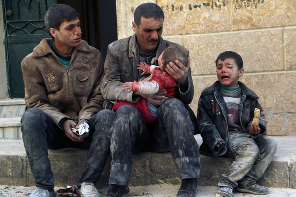 A man holds a baby saved from under rubble, after what activists say was an airstrike by forces loyal to Syrian President Bashar al-Assad in Masaken Hanano in Aleppo, Syria, February 14, 2014. REUTERS/Hosam Katan