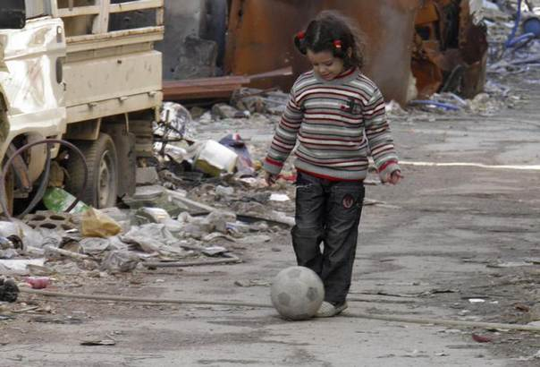 A girl plays with a ball along a street in the besieged area of Homs, January 30, 2014. REUTERS/Thaer Al Khalidiya