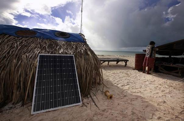Binata Pinata checks the roof of her home as a storm approaches Bikeman islet, off South Tarawa in the central Pacific island nation of Kiribati, a chain of 33 atolls and islands just metres above sea level. Picture May 25, 2013, REUTERS/David Gray
