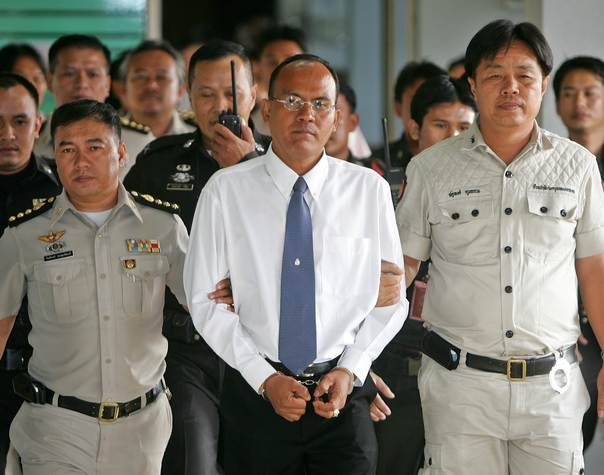 Police Major Ngern Thongsuk (C) is escorted by officials of the Correction Department as he leaves Bangkok Criminal court on Jan. 12, 2006. He was given a three-year jail term for illegal detention of lawyer Somchai Neelaphaichit. However, Ngern was later released on bail and went missing. REUTERS/Chaiwat Subprasom