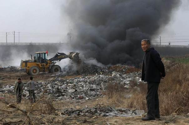 A man looks on as a bulldozer piles up garbage to burn on the outskirts of Baoding, Hebei province, China, March 25, 2014. REUTERS/Stringer