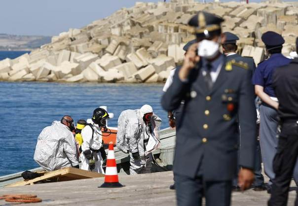 Firefighters arrive on land following their inspection of a boat, on which some 30 bodies were found, after the Italian Navy towed it into the Sicilian harbour of Pozzallo, Italy, July 1, 2014.