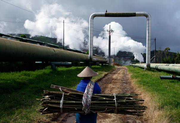 A villager carrying wood for cooking walks near Dipa Energi's Geothermal Power Plant project in Central Java on October 3, 2010. REUTERS/Beawiharta