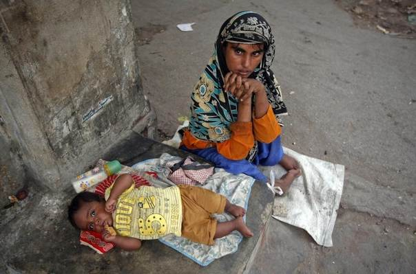 Polio patient Rukhsana, 32, begs with her eight-month old boy Waheed outside a mosque in Karachi July 21, 2012. REUTERS/Athar Hussain