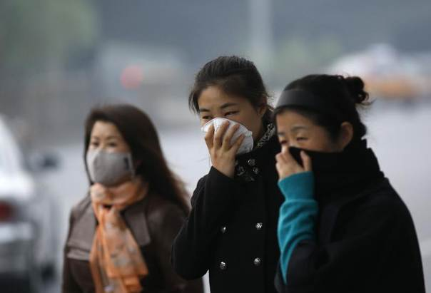 Women wear masks while waiting for a bus on a smoggy day in Beijing, Oct. 28, 2013. REUTERS/Kim Kyung-Hoon