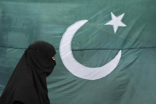 A woman clad in a burqa walks past the national flag of Pakistan,  in Lahore, Pakistan, August 13, 2011. REUTERS/Mohsin Raza