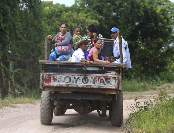 Coffee growers and their families, displaced by the conflict with FARC rebels, travel past a plantation in Serrania de Perija, Cesar province, January 28, 2014. REUTERS/Jose Miguel Gomez