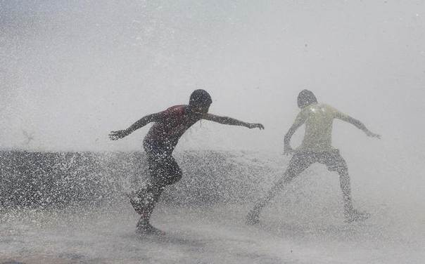 People get drenched in a large wave during high tide at a sea front in Mumbai June 13, 2014. REUTERS/Stringer