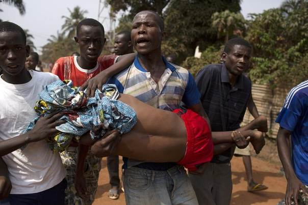 Men carry a boy, who died shortly after from a gunshot wound during a violent confrontation between Muslims and Christians, in Miskine district in the capital Bangui,C.African Republic, January 24, 2014. REUTERS/Siegfried Modola