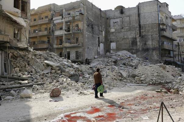 A man walks past damage after what activists said was an air strike by forces loyal to Syria's President Bashar al-Assad in the Al-Maysar neighbourhood of Aleppo, Syria, February 23, 2014. REUTERS/Hosam Katan