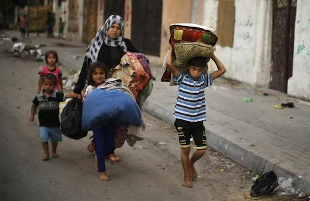 Palestinians carry their belongings as flee their house from what witnesses said were Israeli air strikes, in Gaza City, July 29, 2014. REUTERS/Mohammed Salem