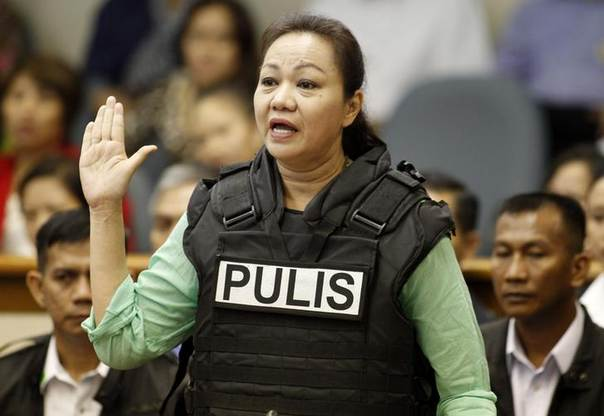 Janet Lim Napoles, wearing a bullet proof vest, takes her oath after arriving at the Senate to testify at a public inquiry in Manila November 7, 2013 REUTERS/Romeo Ranoco