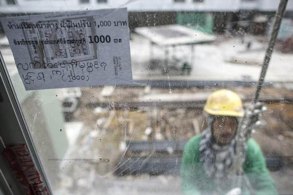 A multi-language sign, written the Thai, Cambodian and Myanmar languages, is seen as a construction labourer works at a building site in Bangkok June 18, 2014 REUTERS/Athit Perawongmetha