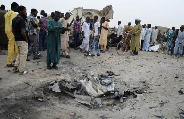 A man takes a picture of a crater after an explosion of one of two vehicles laden with explosives in Ajilari-Gomari near the city's airport, in Maiduguri March 2, 2014. REUTERS/Stringer