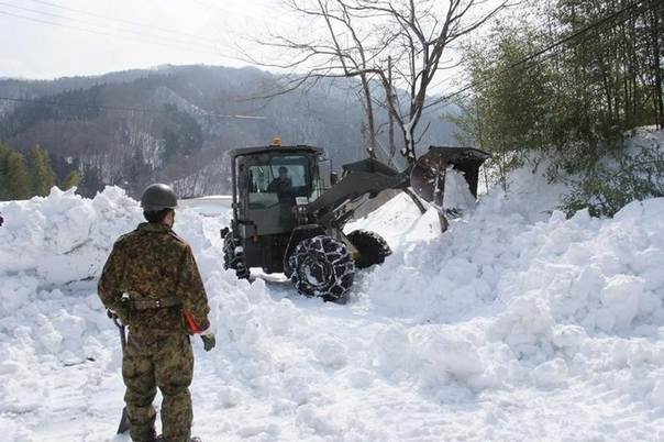 A member of the Japan Ground Self-Defense Force stands near a loader as it removes snow covering a public road in Marumori town, Miyagi prefecture, in this handout picture released on Feb. 18, 2014 by the Japan Ground Self-Defense Force via Reuters.