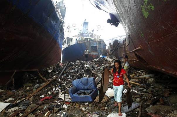 Victims of super typhoon Haiyan pick up pieces of plywood beside cargo ships that were driven ashore by the typhoon at  battered Tacloban city, central Philippines. Picture December 22, 2013, REUTERS/Romeo Ranoco