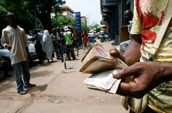In a 2010 file photo, a man checks his money on streets of Conakry, Guinea. REUTERS/Luc Gnago