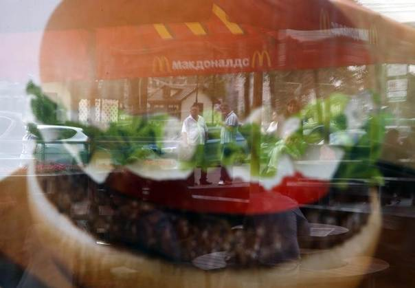 People are reflected in a window of a closed McDonald's restaurant, August 21, 2014. REUTERS/Maxim Zmeyev